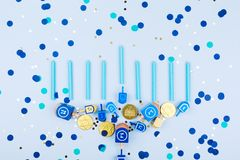 Blue confetti background with menora made of dreidels and chocolate coins. Hanukkah and judaic holiday concept. Horizontal royalty free stock photos