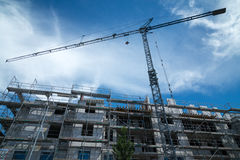 Blue construction crane with a new building in front Royalty Free Stock Images