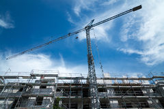 Blue construction crane with a new building in front Royalty Free Stock Photography