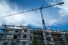Blue construction crane with a new building in front Stock Image