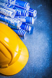 Blue construction drawings yellow building helmet on scratched m Stock Image