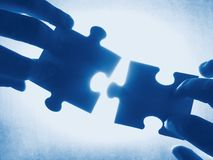 Blue contact. Hands trying to fit two puzzle pieces together Royalty Free Stock Images