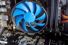 Blue cooler fan with motherboard inside a computer stock photography