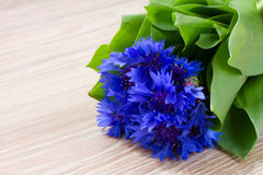 Blue corn flowers on wooden table Stock Photography
