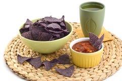 Blue corn tortilla chips with salsa. Blue corn tortilla chips with black bean and sweet corn salsa on braided grass mat Stock Photos