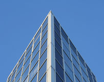 Blue corner. Corner of a modern office building against a clear blue sky. Glass facade Stock Image