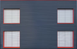 Blue corrugated iron facade with four closed windows Stock Photo