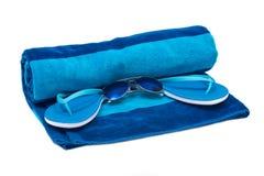 Blue cotton beach towel, flip flops and sunglasses Stock Photo