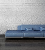 Blue couch against stone wall Stock Photo