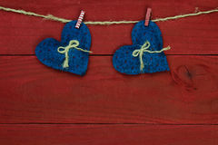 Blue country hearts hanging from clothesline by antique red wooden background Royalty Free Stock Photos