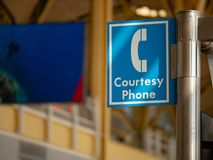 Blue courtesy phone sign hanging high at an airport stock photography