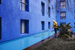 Blue courtyard - maintenance man in yellow slicker. Blue colored building courtyard with a maintenance man in yellow rain slicker cleaning a reflecting water stock photo