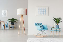 Blue cozy living room. Wooden lamp next to blue rocking chair and table with plant in cozy living room interior with posters Stock Photography