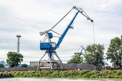 Blue crane in cargo port. Translating coal. Industrial scene Stock Photo