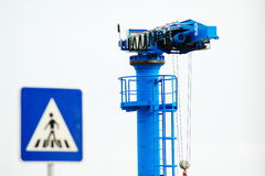 Blue crane crosswalk. A blue heavy lift crane near a crosswalk sign at a port Stock Images