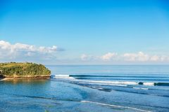 Blue crashing waves in ocean and coconut palms on a beach. Crystal wave in Bali. Blue crashing waves in ocean and coconut palms on a beach. Wave in Bali Stock Images
