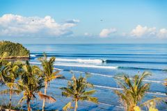 Blue crashing waves in ocean and coconut palms on a cost. Crystal waves in Bali. Blue crashing waves in ocean and coconut palms on a cost Stock Photos