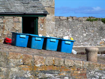 Blue crates on harbour ramp. Blue fishing crates on old stone harbour ramp in Mevagissey, Cornwall royalty free stock photography