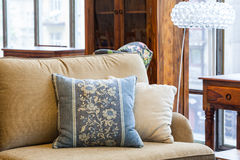 Blue and cream pillows. A light brown sofa with a cream and a blue pillow with flowers Stock Images