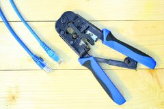 Blue Crimping tool with a computer network cable. The Blue Crimping tool with a computer network cable Royalty Free Stock Images