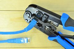 Blue Crimping tool with a computer network cable. The Blue Crimping tool with a computer network cable Stock Photo
