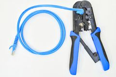 Blue Crimping tool with a computer network cable. Tool Royalty Free Stock Images