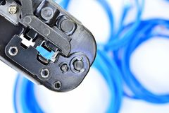 Blue Crimping tool with a computer network cable. Tool Stock Photo
