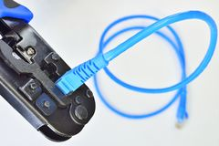 Blue Crimping tool with a computer network cable. On white background Royalty Free Stock Images