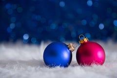 Blue and crimson Christmas balls on white fur with garland light Stock Photos