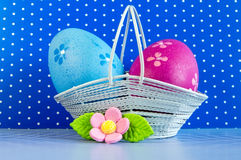 Blue and crimson Easter eggs in a basket with pink flower Stock Images
