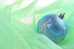 Blue cristmas sphere. On fabrics green background Royalty Free Stock Photo