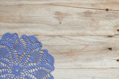 Blue crochet doily on the old wooden table stock photography