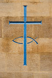 Blue cross. And fish carved into stone, a symbol of christianity Stock Images