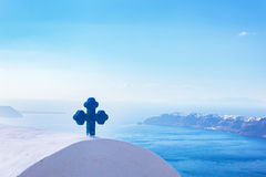 Blue cross on the church roof in Fira on Santorini island, Greece. Aegean sea. view Stock Image