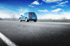 A blue car on the countryside road against sky with clouds Royalty Free Stock Image