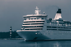 Blue cruise liner. Blue passenger ship sailing in evening in still water. Monochrome Stock Photos