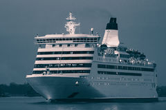 Blue cruise liner. Blue passenger ship sailing in evening in still water. Monochrome Royalty Free Stock Photo