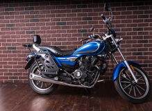 Blue Cruiser Motorcycle in front of Brick Wall Royalty Free Stock Image