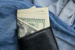 Black leather purse rests on blue trousers. Blue crumpled cloth with a black purse and paper money bills Royalty Free Stock Photos