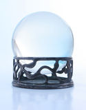 Blue crystal ball on stand. A crystal ball on a metal stand with blue light Stock Images