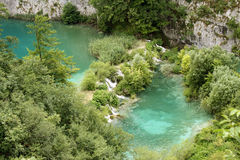 Blue crystal clean lake with fishes and waterfalls. Crystal blue water at the Plitvice lakes having many fishes in the transparent water and waterfalls Stock Photo
