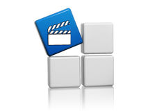 Blue cube with movie icon on boxes. Movie clap icon on 3d blue cube over grey boxes Stock Photo