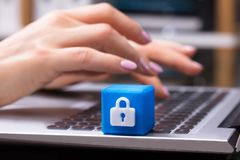 Blue Cubic Block With Lock Symbol. Businesswoman Working On Laptop With Blue Cubic Block Showing Lock Symbol stock photography