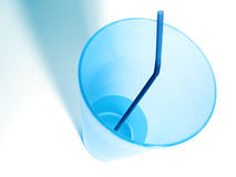 Blue Cup. A tall, plastic blue cup with a blue straw and water. Blue shadows stock image