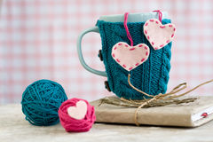 Blue cup in a blue sweater with felt hearts stock photo
