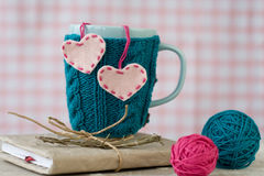 Blue cup in a blue sweater with hearts Royalty Free Stock Photography