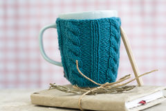 Blue cup in a blue sweater standing on an old notebook Royalty Free Stock Photography