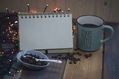 Notepad, blue cup and coffee beans in a bowln Royalty Free Stock Image