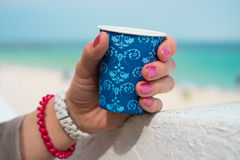 Blue cup of coffee in a female hand. On a beach background. The hand rests on a white parapet. On the wrist white and red bracelets Stock Photos