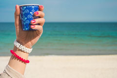 Blue cup of coffee with an ornament. In the left female hand against the background of the beach. On the women's hand red and white bracelets. On nails red Royalty Free Stock Photos
